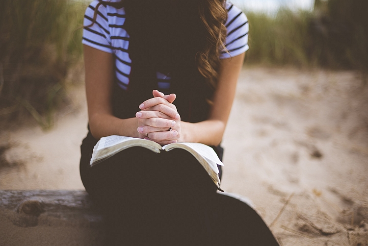 A lady praying with a book on her knees
