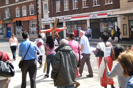 A crowd walking through Uxbridge with a wooden cross wrapped in red fabric being carried by one member of the crowd