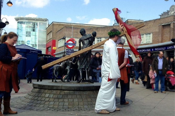 A man dressed as Jesus in a white robe with a crown of thorns carrying a wooden cross outside Uxbridge underground station