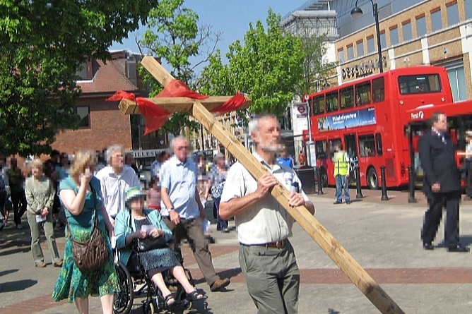 A man carries a wooden cross wrapped in red fabric down Uxbridge High Street while a crowd follows behind