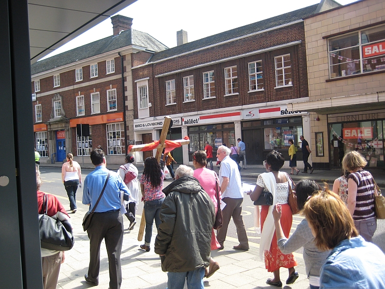 A crowd walking through a town centre with one carrying a cross as part of a walk of witness
