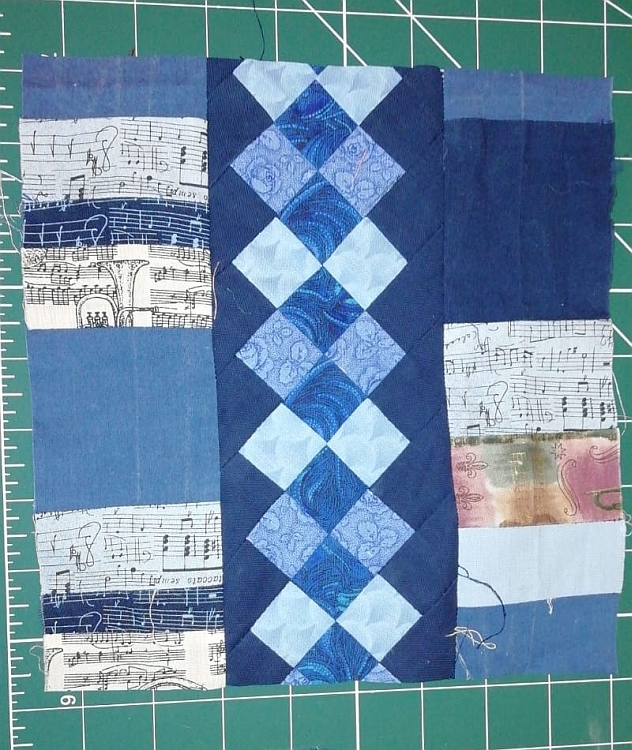 A patchwork square with various pieces of blue-coloured fabrics