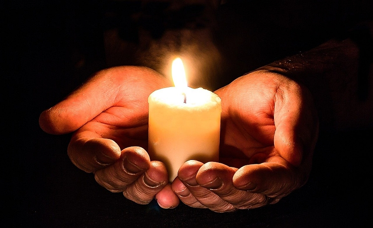 A candle being cradled in two hands