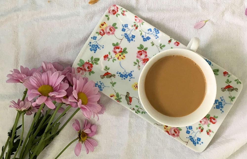 A cup of tea on a flowery tray with a bunch of pink flowers next to it