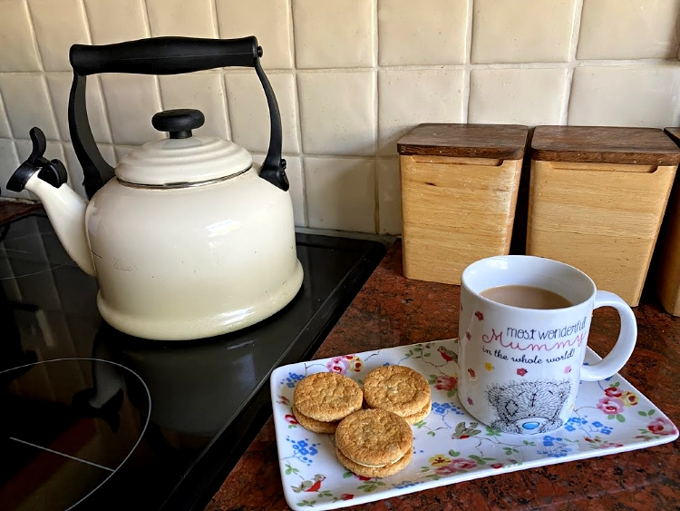 A cup of tea on a tray with biscuits next to a hob kettle