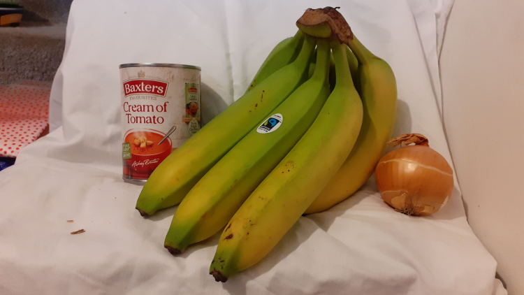 A bunch of giant bananas next to a normal-sized tin of soup and an onion
