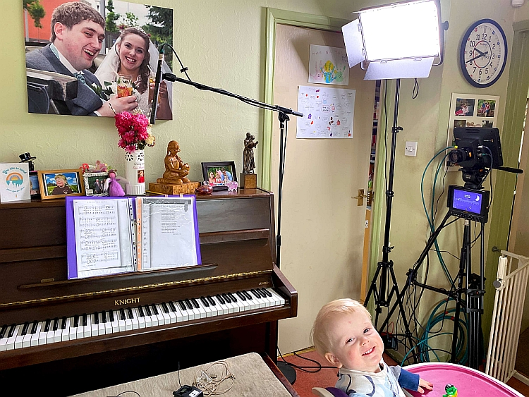 A piano with a microphone over it, mic packs on the piano stool, lights and camera set up and a toddler sitting in a highchair in the foreground