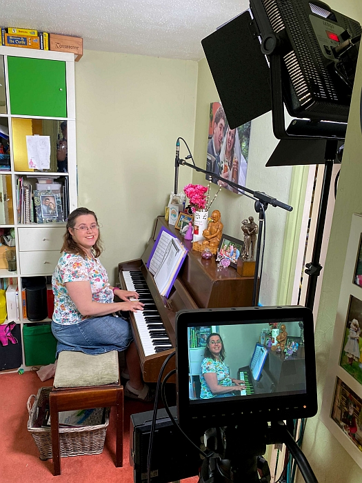 A woman sitting at a piano with a light and camera in the foreground showing her being filmed