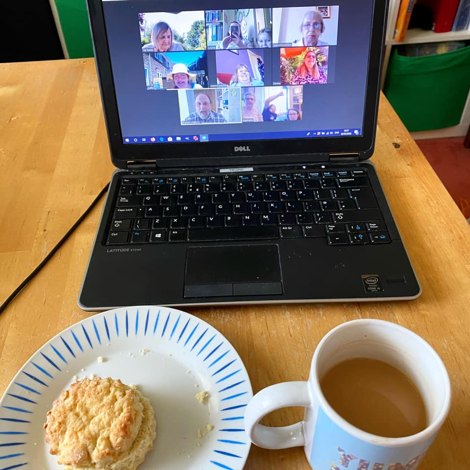 A cup of tea and a plate with a scone in front of a laptop showing the church Zoom coffee morning