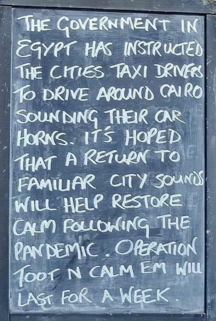 """A chalkboard with a message reading """"The government in Egypt has instructed the cities taxi drivers to drive around Cairo sounding their car horns. It's hoped that a return to familiar city sounds will help restore calm following the pandemic. Operation Toot N Calm Em will last for a week."""""""