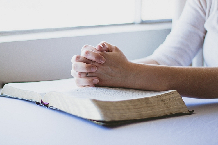Hands clasped in prayer on top of a book