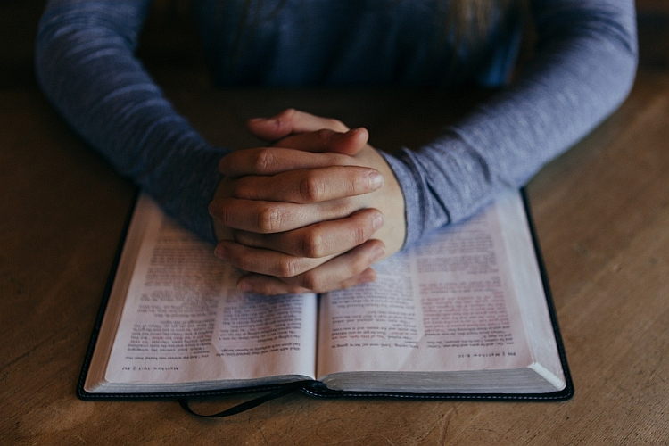 Hands clasped on top of a BIble