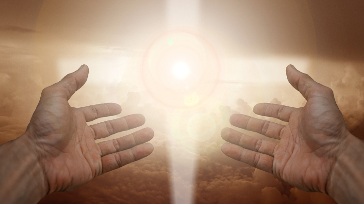 Outstretched hands with a glowing cross between them