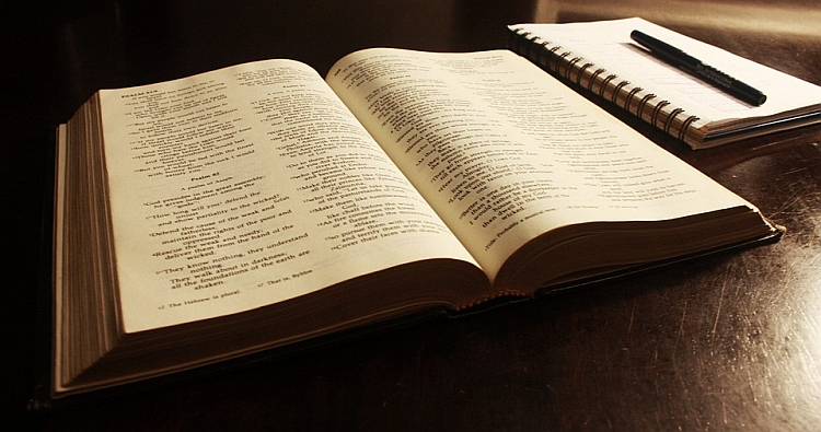 A Bible on a table with a notebook and pen next to it