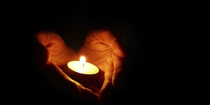 Hands held together in a heart shape holding a lit tealight candle