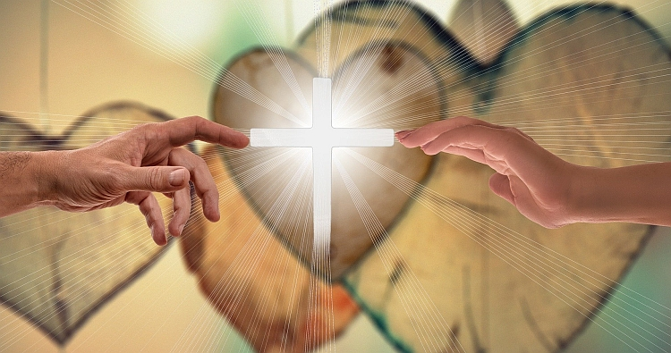 Two hands touching each side of an illuminated cross with wooden hearts in the background