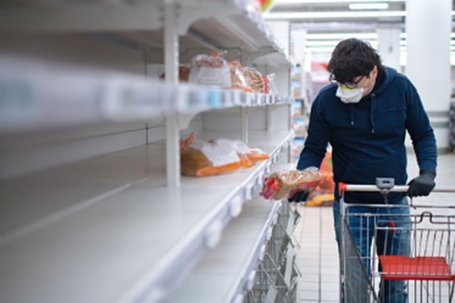 A man with a mask picking up a loaf of bread from near-empty supermarket shelves