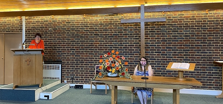 Two church members at the front of the chapel - one at the lectern, the other sitting at the communion table