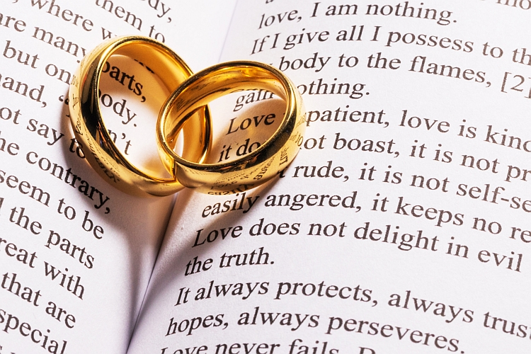 Two wedding rings on top of a Bible open at 1 Corinthians 13
