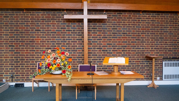 The inside of the chapel looking at the communion table (with flowers on) and the cross on the back wall