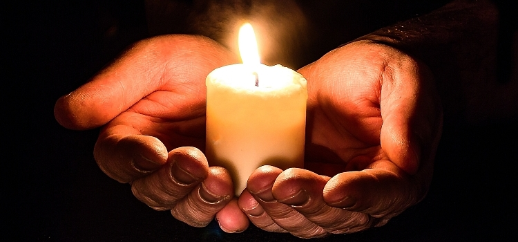 Cupped hands holding a lit candle