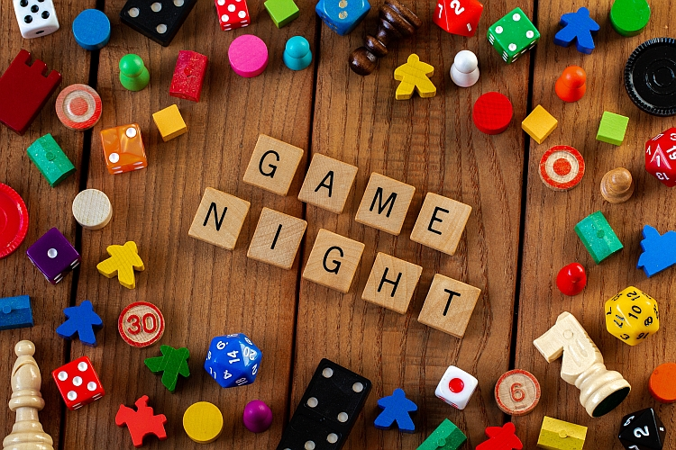 """Game Night"" spelled out in wooden letter tiles. Surrounded by dice, cards, and other game pieces on a wooden background"