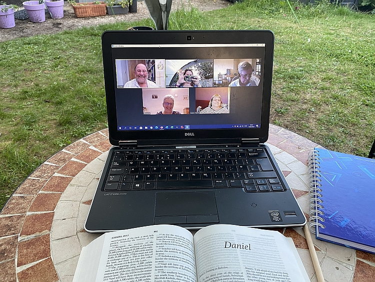 A laptop showing a Zoom meeting with a Bible open to Daniel in front of it