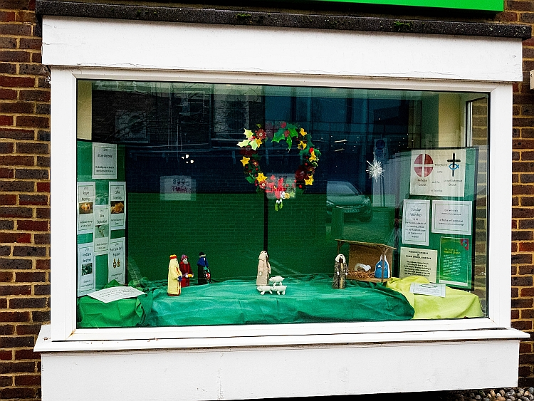 The Christmas window at Christ Church with a nativity scene and the community Christmas wreath hanging above it
