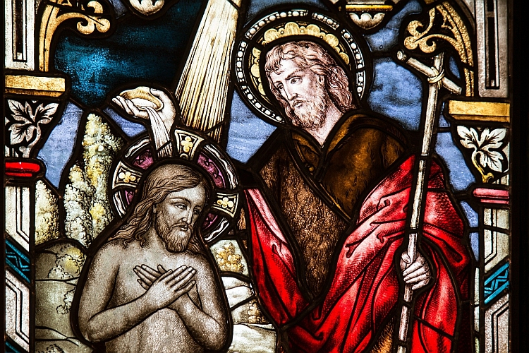 A stained glass window showing John baptising Jesus