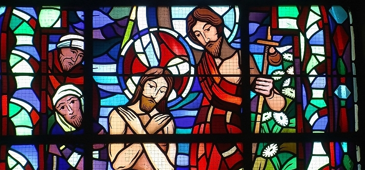 A stained glass window depicting John baptising Jesus