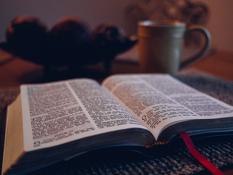 An open Bible on a table with a mug in the background