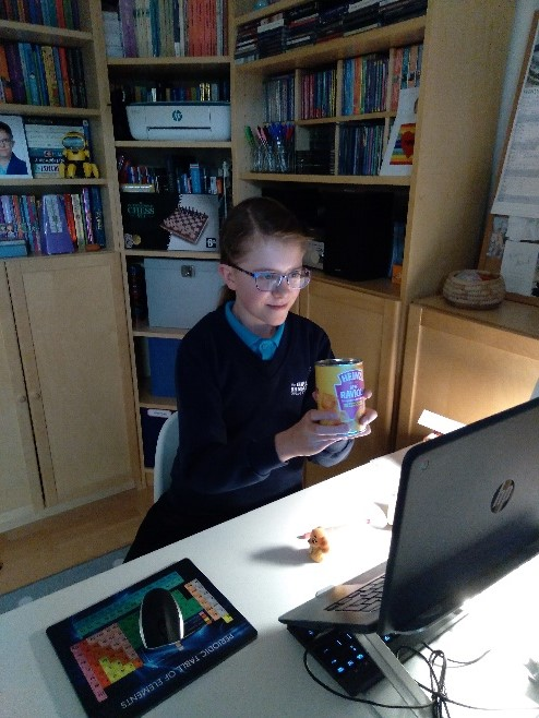 A girl in a GB uniform holding a tin of ravoli in front of her computer screen