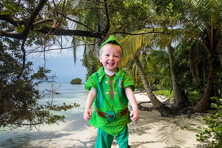 A little boy dressed as Peter Pan in front of an island background