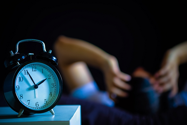 An alarm clock in the foreground with a man in the background suffering from insomnia