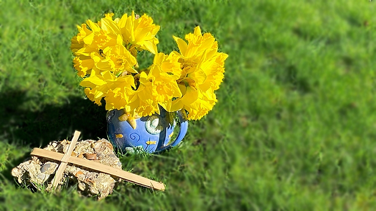 A vase of daffodils on grass with a stone and a palm cross in front