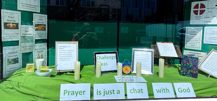 """A window display showing some prayer challenges and the words """"prayer is just a chat with God"""""""