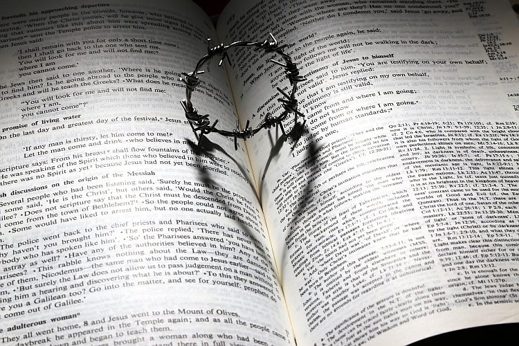 A small crown of thorns on a Bible with the shadow casting the shape of a heart