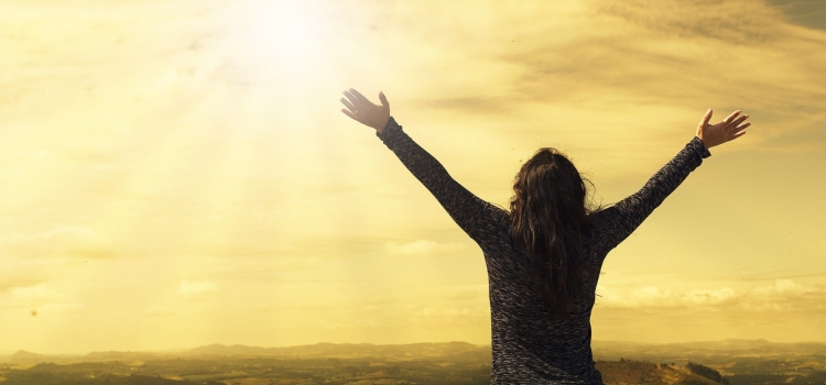 A silhouetted person with arms outstretched towards a yellow sky