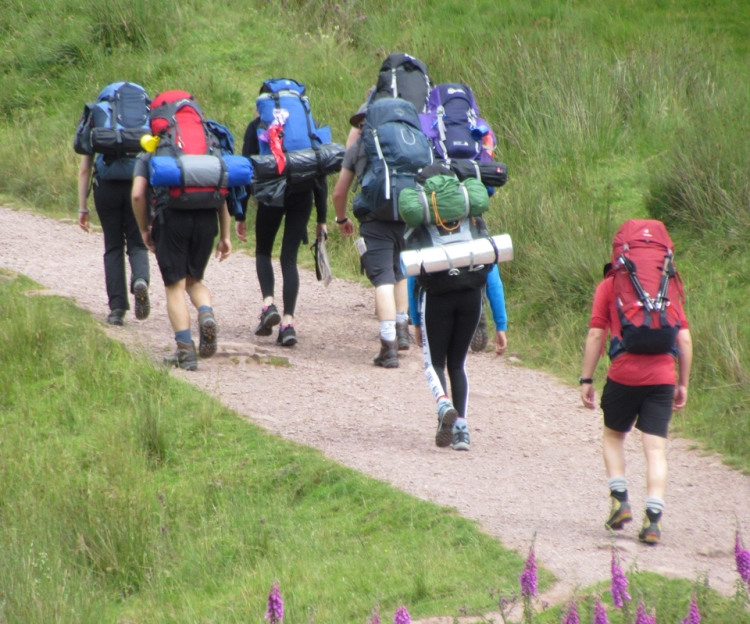 A group of young people laden with backpacks and camping equipment