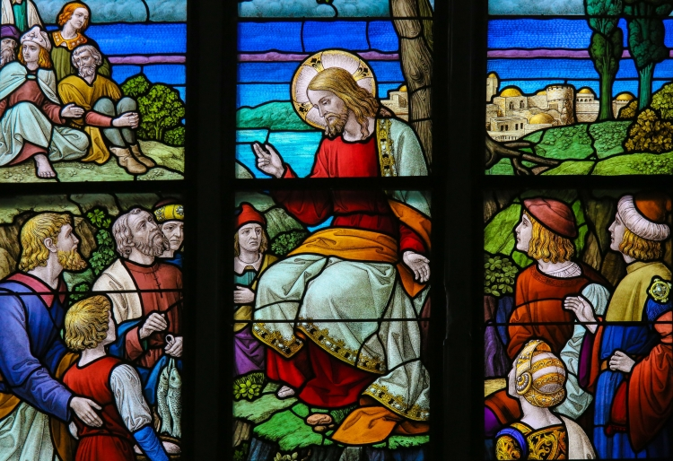 Stained Glass window depicting the miracle of Jesus feeding the multitude with loaves of bread and fish in the Cathedral of Saint Rumbold in Mechelen, Belgium.