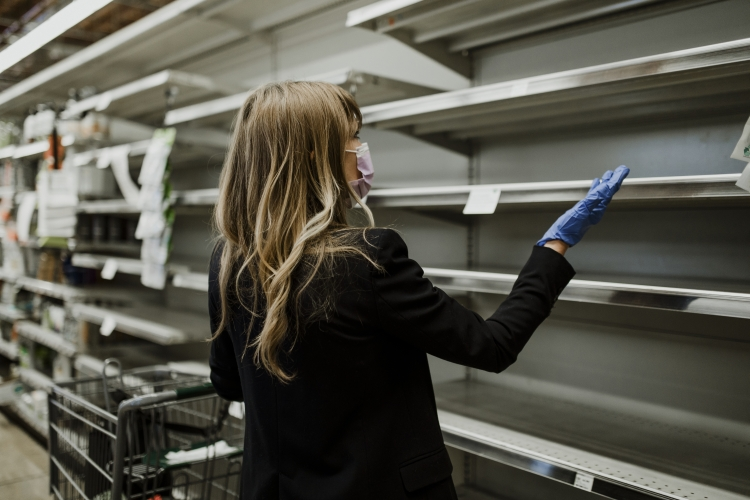 Woman with empty shelves in a supermarket during coronavirus pandemic
