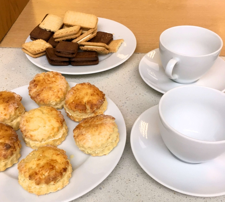 Cheese scones and biscuits on plates with white cups and saucers laid out ready for a coffee morning