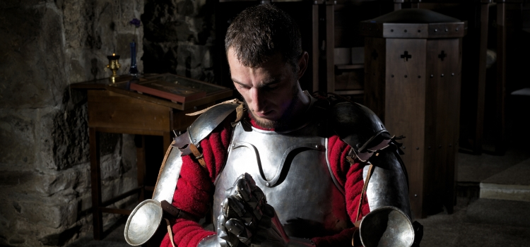 Knight Kneeling On His Knees With Bowed Head And Praying Hands