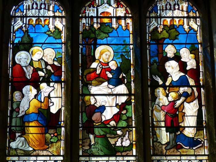 A stained glass window depicting Jesus with children