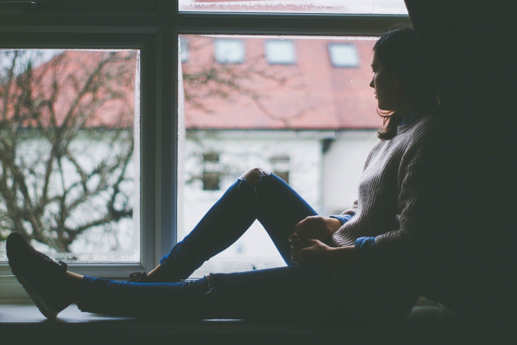A woman sitting next to a big window, looking out