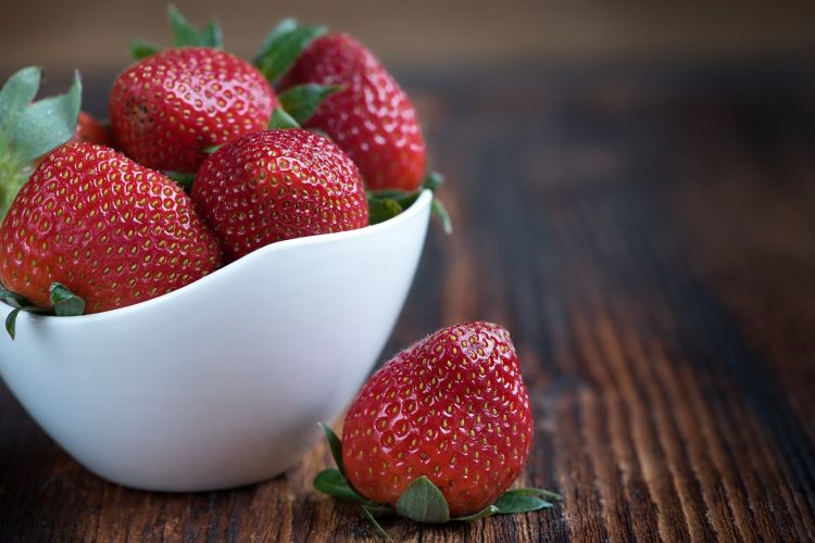 A bowl of strawberries o a table