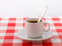 A cup of coffee on a red and white checked tablecloth