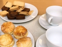 Biscuits and scones on white plates next to white cups and saucers