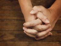 Hands clasped in prayer on a wooden table